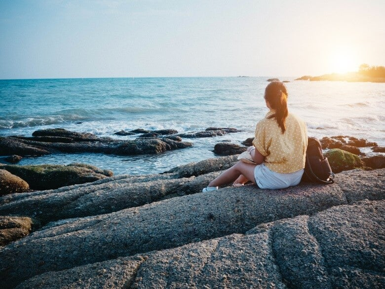woman sitting on a rock stares at the sea