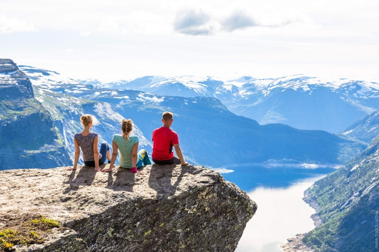 friends sitting on Trolltunga in Norway