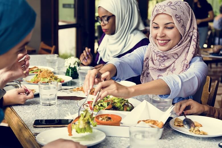 Three women enjoying eating while living in the UAE