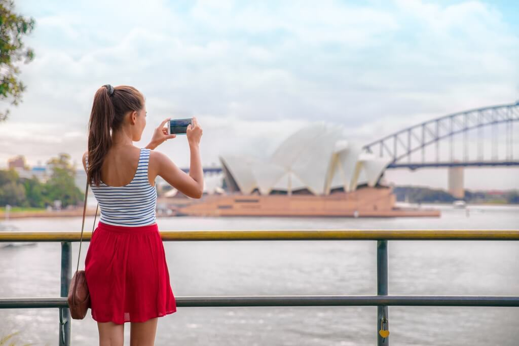 Woman taking photo of the landscape after moving to Sydney