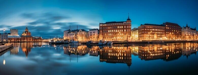 Buildings lit up near river in Helsinki