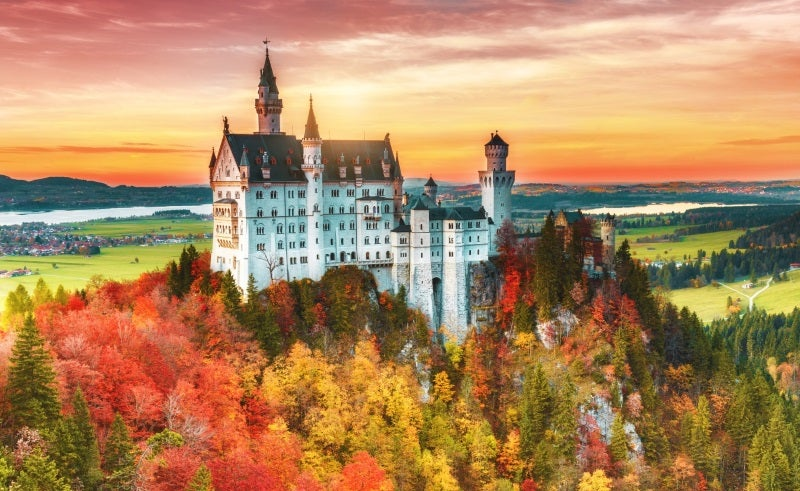 Neuschwanstein Castle on top of a hill in autumn, during a sunset, showing why moving to Germany is a great idea