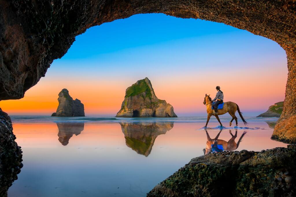 sunset on Wharariki beach, as a woman rides a horse