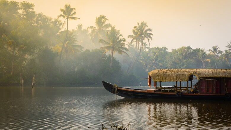 A traditional house boat is anchored on the shores of a fishing lake in Kerala's Backwaters, India