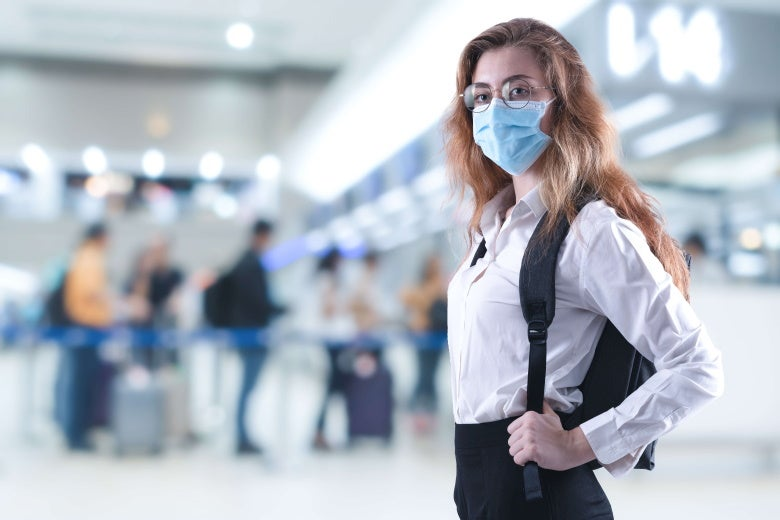 woman with mask stands in airport