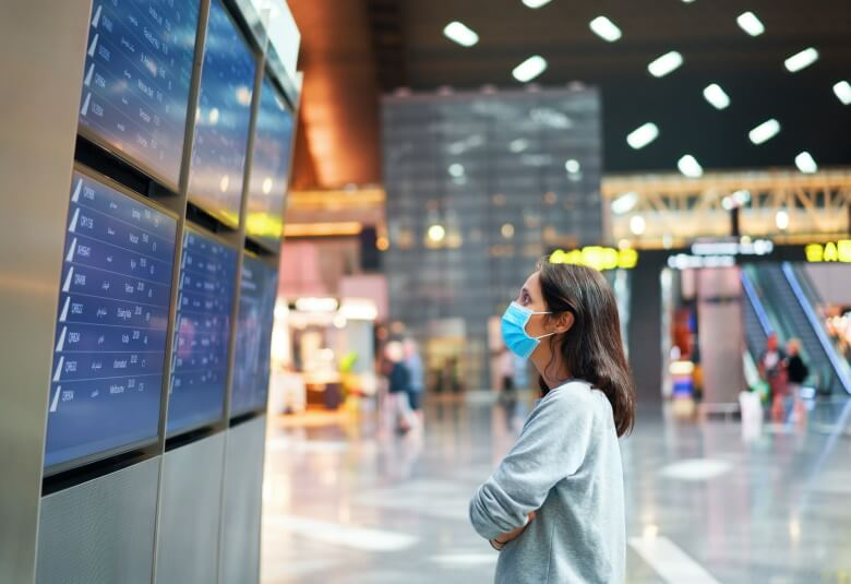 woman looking at flight schedule in airport
