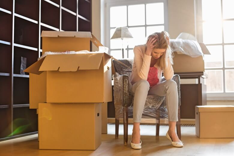 stressed woman next to cardboard boxes