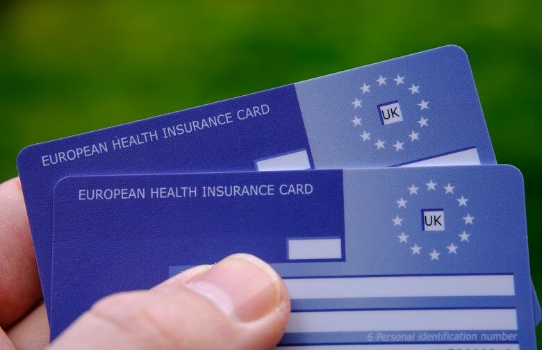 Someone holding two European Health Insurance Cards