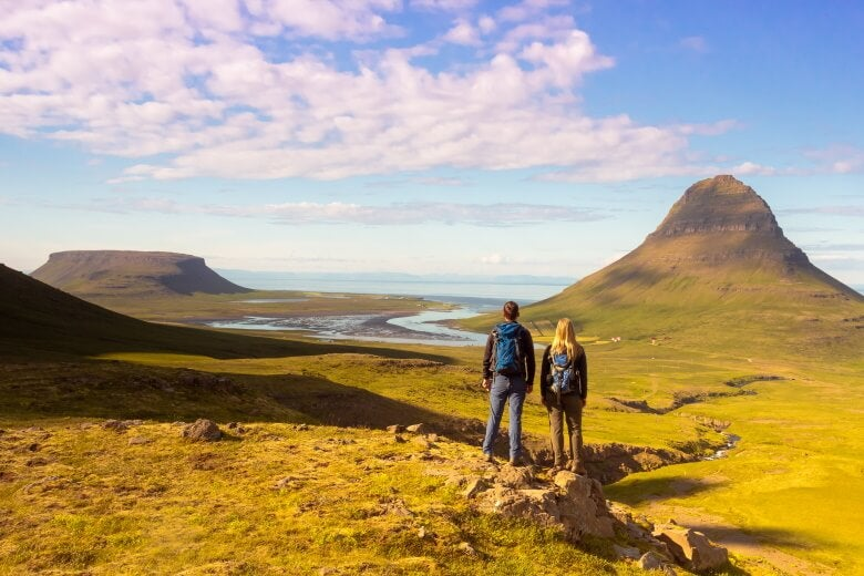 couple looking out at the Kirkufell mountain, in Iceland