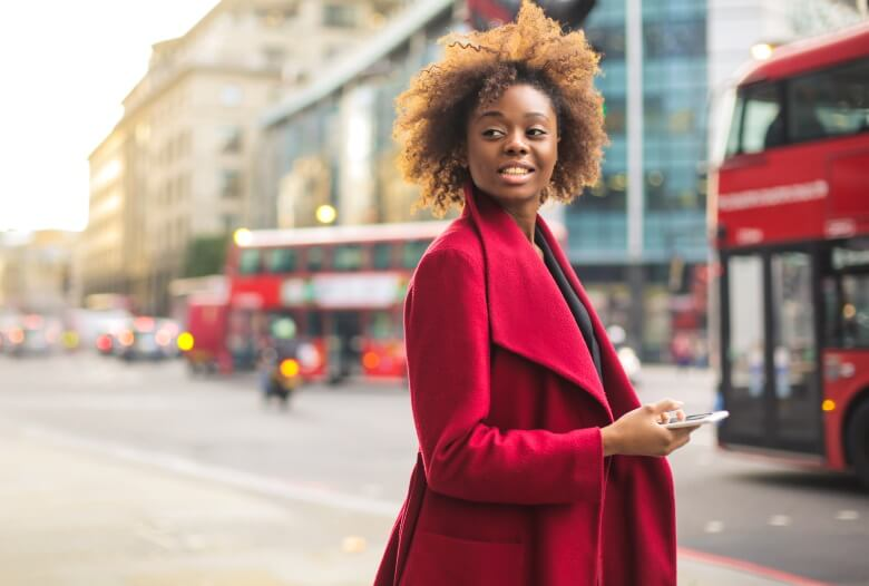 woman standing in front of a red bus in london