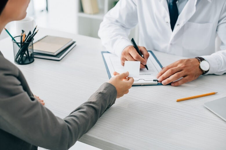 Person handing over health insurance card